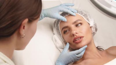 Beauty Surgeon Checking Female Face at Beauty Clinic