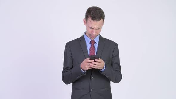 Thumbnail for Studio Shot of Happy Businessman Using Phone