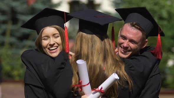 Thumbnail for University Friends Hugging Warmly Congratulations on Successful Graduation