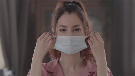 Joyful Woman Takes Off Surgical Mask On Her Face And Looks Directly At The Camera