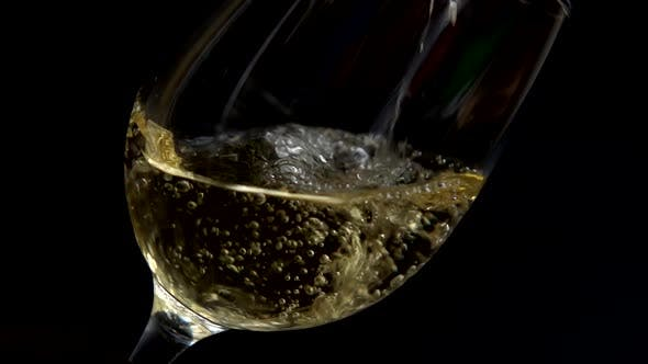 Wine is poured into a glass on a black background. Slow motion.