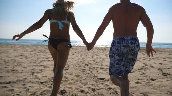 Cover Image for Young Couple of Lovers Running at Beach To Sea Holding Hands. Happy Girl and Boy Having Fun Together