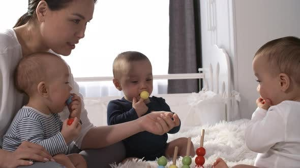 Asian Woman Removing Toy from Baby's Mouth