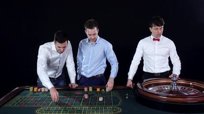 Young Man Playing Roulette in the Casino. Dealer Takes Bets. Black