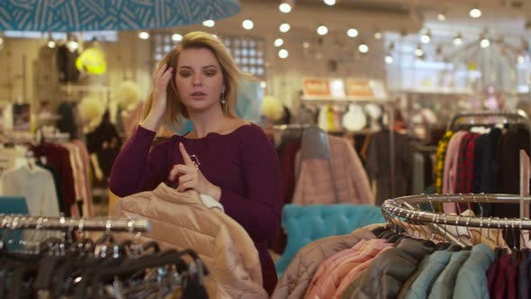 Thumbnail for Girl Quickly Takes Clothes Off the Hanger in the Store