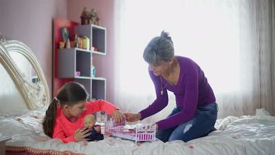 Mom and daughter play dolls on the bed. Mother's Day