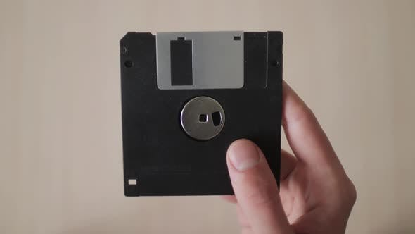 Male Hand Holds Up Black Floppy Disk