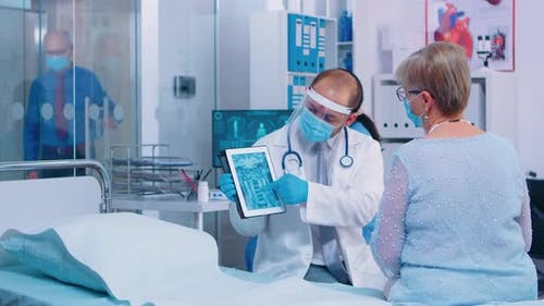 Physician Showing Retired Woman Radiology Scan on Digital Tablet