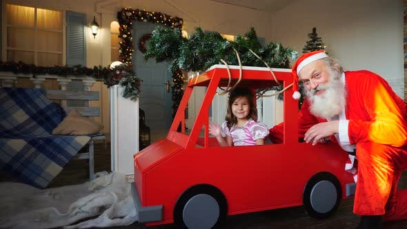 Thumbnail for Funny Santa Claus Playing with Little Princes Waving Hand in Red Car.