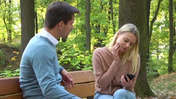 Thumbnail for A Man and a Woman Sit in a Park, the Woman Is Absorbed with Her Smartphone, the Man Is Angry at Her
