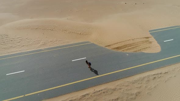 Thumbnail for Aerial view of woman doing exercise in road cover by sand on Abu Dhabi, U.A.E