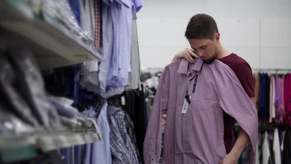 Consumer Man is Viewing Shirt in Trade Area of Clothing Shop