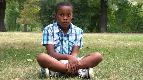 Thumbnail for A Young  Black Boy Sits on Grass in a Park and Looks Seriously at the Camera