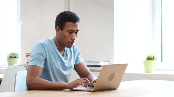 Thumbnail for Serious Black Man Looking Toward Camera, Working on Laptop