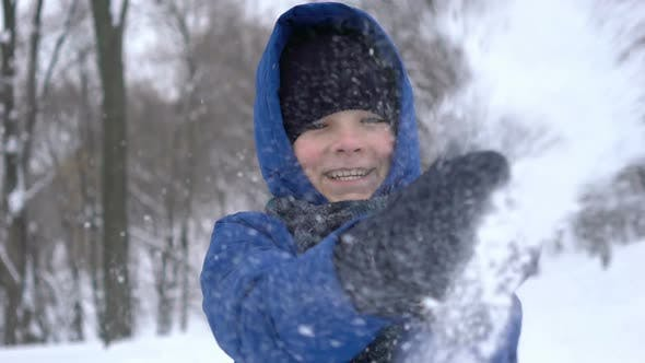 Thumbnail for Portrait of a Young Guy Clapping Hand with Snow in the Winter Forest
