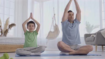 Father and Son Practicing Yoga in Living Room