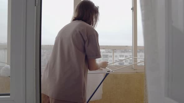 Woman Dries Clothes on the Balcony