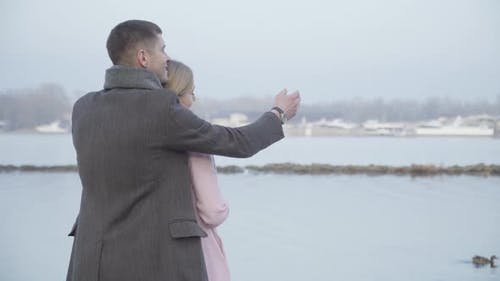 Romantic Caucasian Couple Hugging on Riverbank and Chatting. Back Side View of Younger Man and Older