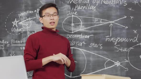 Asian Physicist Presenting New Project at Chalkboard