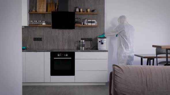 Pandemic Covid-19. A Man in a Protective Suit, Disinfects the Room. Special Sanitizer, Sprayed on