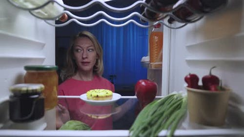 A Beautiful Young Woman Opens the Refrigerator Door at Night Looks Around with Caution and is Happy