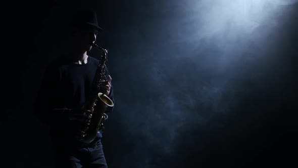 Silhouette the Men Musician Improvising on the Saxophone. Illumination Spotlight