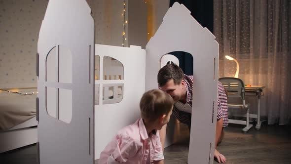 Glücklicher fröhlicher und lachender Junge mit jungem Vater, der nachts im Spielzeughaus im Kinderzimmer spielt