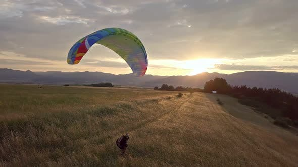 Thumbnail for Playing with Paraglider in Golden Meadow at Sunset