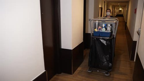 Masked Chambermaid Walking with Cleaning Trolley