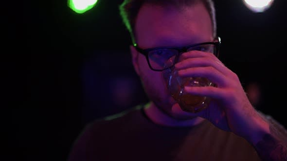 Thumbnail for Portrait of Sad Man Drinking Alcohol at the Disco Close Up. Man in Glasses Looking at Camera