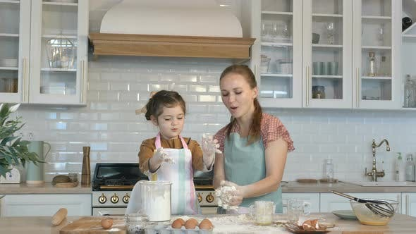 Thumbnail for Funny Daughter and Mother Make Dough for Pie at Large Table