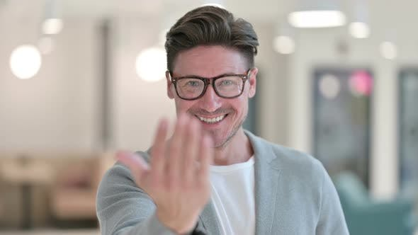 Thumbnail for Portrait of Smiling Middle Aged Man Pointing and Inviting