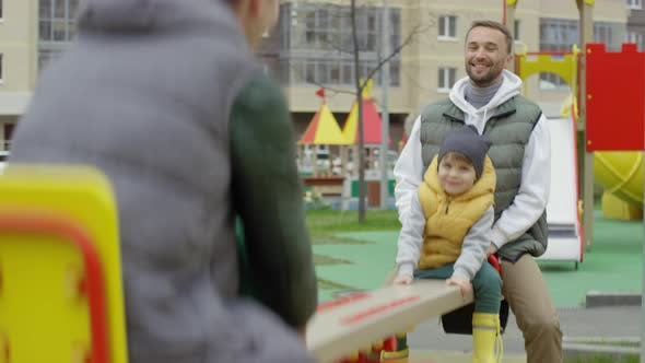 Thumbnail for Two Caucasian Dads Enjoying Seesaw Ride with Young Sons