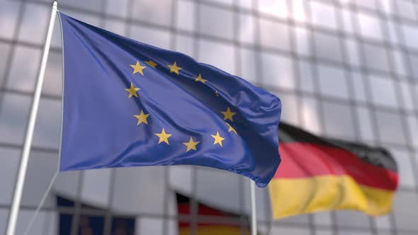 Waving Flags of the EU and Germany in Front of a Modern Skyscraper
