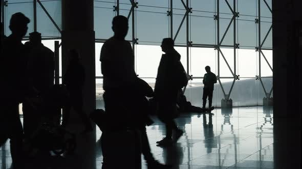 Silhouette of Passing People in Airport Terminal