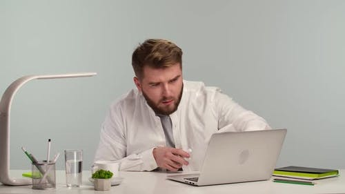 Young Man Freelance Worker Disinfects Laptop with Alcohol Disinfectant Spray and Napkin