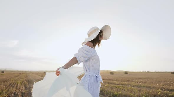 Thumbnail for Attractive Girl in a Long Dress Sunglasses Big Hat with a Scarf Spins Around Herself