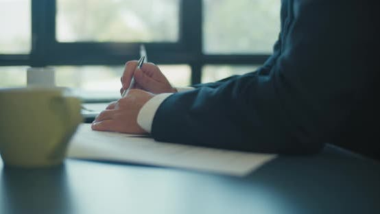 Thumbnail for Close up of hands of businessman holding a pen and lie on the documents during a business meeting.