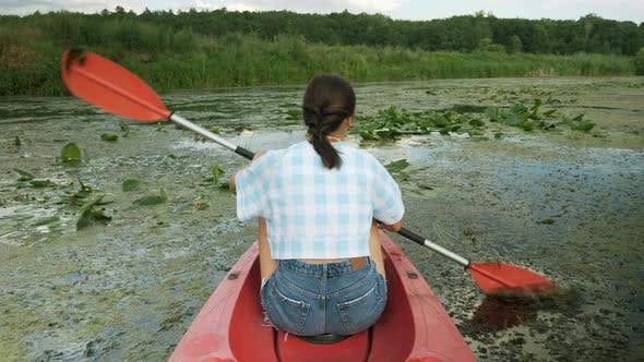 Thumbnail for Back shot of young woman floating in red canoe on river. Boat on the river