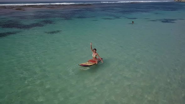 Woman Relaxing in the Sea on a Surfboard