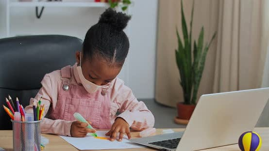 Concentrated African American Schoolgirl Child Sitting at Table at Home Draws Picture with Pencil