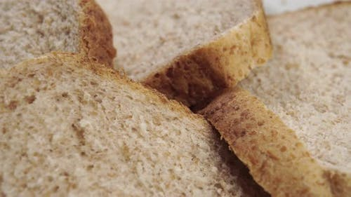 Rough textured slices of fresh wheat baked integral bread with crust