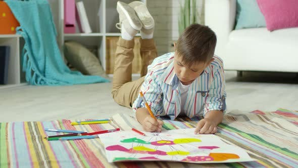 Thumbnail for Little Boy Lying on Floor at Home and Drawing Picture