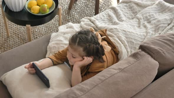 Thumbnail for Little Girl with Bows and Plaid Watches Cartoons on Phone