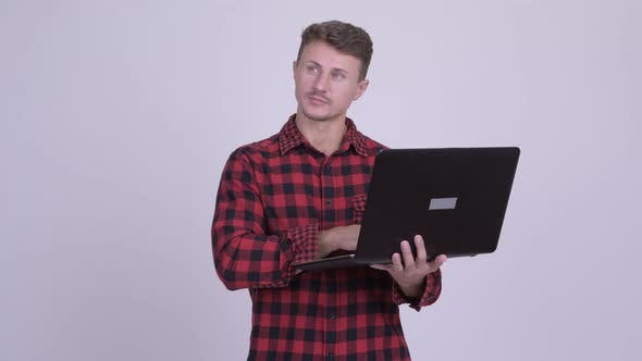 Thumbnail for Happy Bearded Hipster Man Thinking While Using Laptop