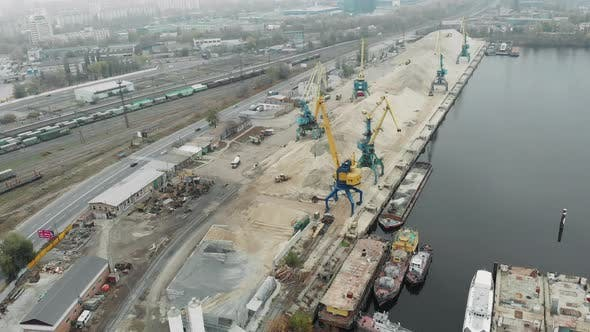Aerial view of port working cranes extracting sand from iron barge and scow