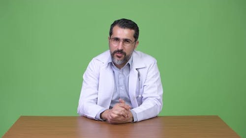 Handsome Persian Bearded Man Doctor Talking and Giving Consultation
