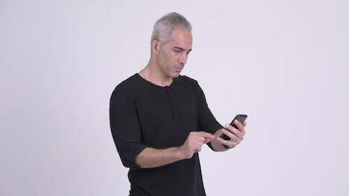 Happy Handsome Persian Man Using Phone and Getting Good News