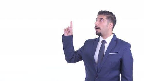 Glückliche bärtige persische Geschäftsmann zeigen nach oben und suchen aufgeregt