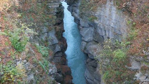 Breathtaking View on Deep Cleft Between Rocks with River
